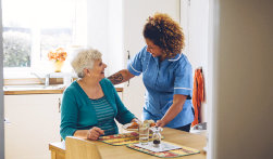 caregiver serving food to adult woman