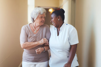 happy female caregiver and senior woman walking together