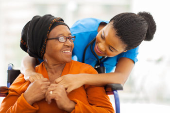 caregiver assisting elderly woman in hospital