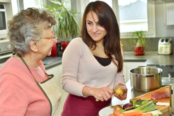 caregiver preparing meal for the elderly woman