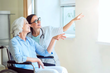 caregiver and elderly woman pointing at the window